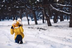 美丽的年轻母亲和她的小女儿在背上继续冬天的森林里拥抱 库存照片