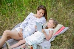 美丽的年轻母亲和她的小女儿白色礼服的获得乐趣在一顿野餐在一个夏日 他们说谎在地毯和读 免版税库存图片