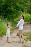美丽的年轻母亲和她的小女儿白色礼服的获得乐趣在野餐 他们在一条路站立在公园,举行 免版税库存图片