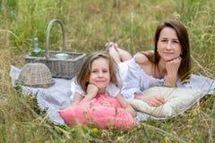 美丽的年轻母亲和她的小女儿白色礼服的获得乐趣在野餐 他们在草的格子花呢披肩说谎和 库存图片