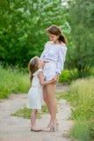 美丽的年轻母亲和她的小女儿白色礼服的获得乐趣在野餐 他们在路站立在公园,拥抱和 免版税库存照片