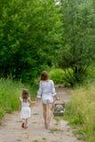 美丽的年轻母亲和她的小女儿白色礼服的获得乐趣在野餐 他们沿路走在公园 免版税库存图片