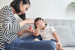 美丽的年轻母亲绘指甲给她逗人喜爱的矮小的女儿 图库摄影