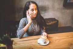 美丽的年轻深色的女孩谈话在手机在木桌上在窗口和饮用的咖啡附近在装饰的咖啡馆 库存图片