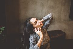 美丽的年轻深色的女孩谈话在手机在木桌上在窗口和饮用的咖啡附近在装饰的咖啡馆 免版税库存图片