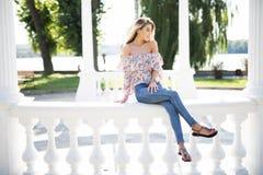 美丽的年轻深色的妇女坐扶手栏杆在公园 图库摄影