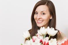 美丽的年轻深色的妇女接近的画象在手上拿着白色和桃红色郁金香明亮的花束,微笑 库存照片