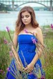 美丽的年轻深色的妇女画象草甸的在河附近 免版税库存照片