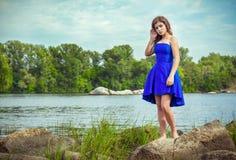 美丽的年轻深色的妇女,佩带的典雅的蓝色礼服画象  免版税库存照片