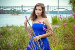 美丽的年轻深色的妇女,佩带的典雅的蓝色礼服画象  免版税库存图片