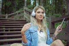 美丽的年轻白肤金发的在耳机的行家妇女听的音乐在有片剂的公园在手上,坐木步 免版税库存照片