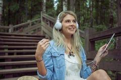 美丽的年轻白肤金发的在耳机的行家妇女听的音乐在有片剂的公园在手上,坐木步 免版税图库摄影