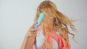 美丽的年轻白肤金发的女孩不能称呼她长的头发,杂乱发型 影视素材