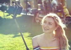 美丽的年轻白肤金发的女孩在一个城市公园在做在智能手机的一个晴天selfie 免版税库存照片