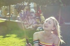 美丽的年轻白肤金发的女孩在一个城市公园在做在智能手机的一个晴天selfie 图库摄影