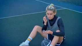 美丽的年轻白肤金发的女性蓝球运动员做构成和坐与球,佩带的运动服的地面 股票视频