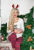 美丽的年轻白肤金发的妇女圣诞节睡衣的和有驯鹿垫铁的,坐步和拿着曲奇饼装饰 免版税库存照片