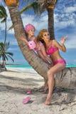 美丽的年轻白肤金发的妇女星期一坐一棵棕榈树的树干与女儿的,小女孩公主 免版税图库摄影