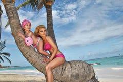 美丽的年轻白肤金发的妇女星期一坐一棵棕榈树的树干与女儿的,小女孩公主 库存图片