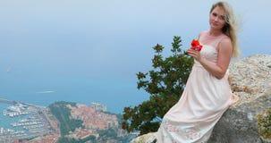 美丽的年轻白肤金发的妇女画象有吹在她的头发的风的坐岩石 影视素材