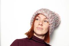 美丽的年轻红头发人女孩被隔绝的画象紫色毛线衣和桃红色被编织的帽子的有绒球的穿戴了斜向一边微笑 库存照片