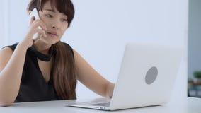 美丽的年轻自由职业者的亚裔在手提电脑和谈的顾客的妇女微笑的工作有电话电话的 股票录像