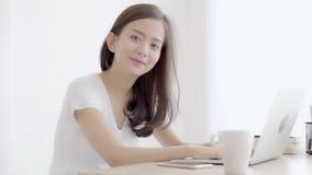 美丽的年轻自由职业者的亚裔妇女微笑的研究手提电脑在有专家的书桌办公室 股票录像