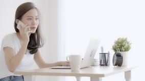 美丽的年轻自由职业者的亚裔妇女微笑的运转的手提电脑和谈的顾客有电话电话的在办公室,女孩使用n 股票录像