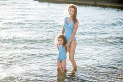 美丽的年轻获得母亲和的女儿基于海的乐趣 他们在同一泳装和微笑的水中站立 免版税库存图片
