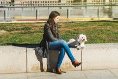 美丽的年轻西班牙妇女和她的狗 免版税图库摄影