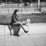 美丽的年轻西班牙妇女和她的狗 免版税库存照片
