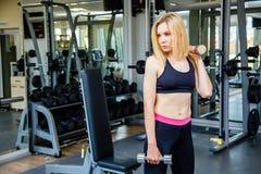 美丽的年轻运动的妇女照片  健身与哑铃的女孩训练在体育俱乐部用锻炼设备 库存照片