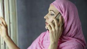 美丽的年轻阿拉伯妇女支持窗口和谈话在手机 股票录像