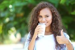 美丽的年轻非裔美国人的妇女饮用奶 库存图片