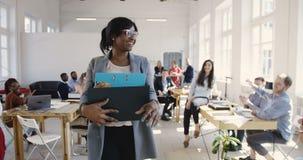 美丽的年轻黑人女性经理运载的办公室箱子,聘用为新的工作、不同种族的同事欢迎和微笑 影视素材