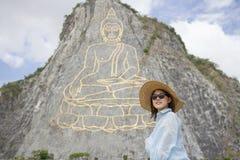 美丽的年轻aisan妇女在山背景的站立和微笑与菩萨,菩萨金黄雕象的山坡的 免版税图库摄影