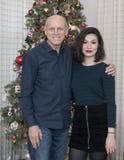 美丽的年轻Amerasian妇女在与她的父亲的一棵圣诞树前面摆在了 免版税库存照片