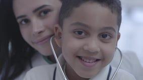 美丽的年轻caucasion妇女画象有看在照相机微笑的英俊的混血儿男孩的 孩子有听诊器 影视素材