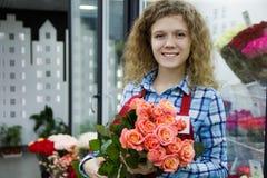 美丽的年轻smilling的妇女卖花人卖玫瑰的bouqet在花店的 图库摄影