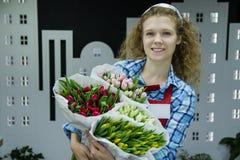 美丽的年轻smilling的妇女卖花人卖郁金香的bouqet在花店的 免版税库存图片