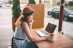 美丽的幼小白种人小狗坐在一个咖啡馆的一个大阳台在夏天在帽子和板材的一张木桌上使用技术,w 免版税库存照片