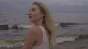 美丽的幼小白肤金发的妇女海滩若虫接近的画象在白色礼服的在有波浪的海附近在一愚钝阴沉期间 影视素材