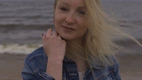 美丽的幼小白肤金发的妇女海滩若虫接近的画象在白色礼服的在有波浪的海附近在一愚钝阴沉期间 股票录像