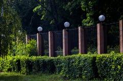 美丽的庭院操刀与砖篱芭 库存照片