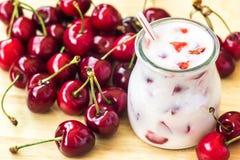 美丽的开胃菜红色樱桃果子圆滑的人 酸奶鸡尾酒 关闭 自然戒毒所 液体冰淇凌 樱桃milksha玻璃  库存照片