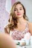 美丽的微笑的十几岁的女孩梳她长的柔滑的头发 库存图片