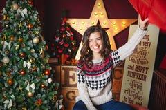 美丽的微笑的卷曲妇女画象临近圣诞树 庆祝 滑稽 羽绒枕头 库存照片