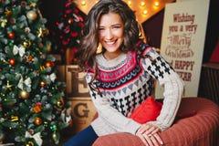 美丽的微笑的卷曲妇女画象临近圣诞树 庆祝 库存照片