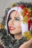 美丽的微笑的埃及妇女在看投掷圣诞节圈子树的圣诞老人服装 免版税库存图片