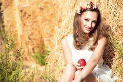 美丽的微笑的女孩佩带的白色夏天坐在干草堆和拿着一个红色苹果的礼服和花卉顶头花圈 免版税库存照片